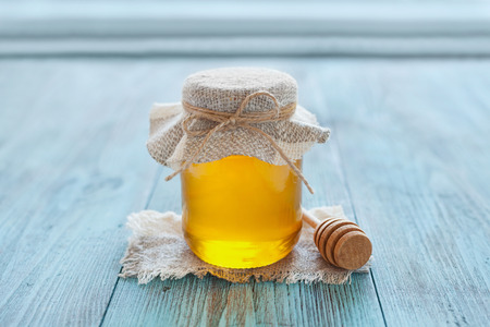42038748 - natural honey in a pot or jar with twine tied in a bow and honey dipper on a blue wooden background