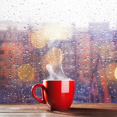 25362698 - steaming cup of coffee over a cityscape background
